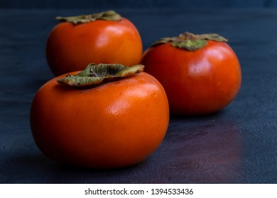 persimmons in a line horizontal orientation on grey textured background