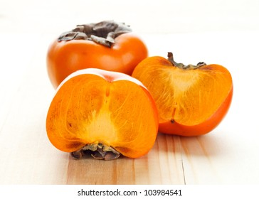 Persimmons on a wooden substrate