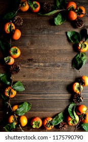 Persimmons.frame.on the black wooden background