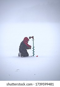 Persisten ice fishing man sitting in the middle of a blizzard on a frozen lake in Lapland, Finland