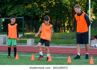 Persistent teen sports boys in orange uniform running among plastic cones during football exercises at the stadium.