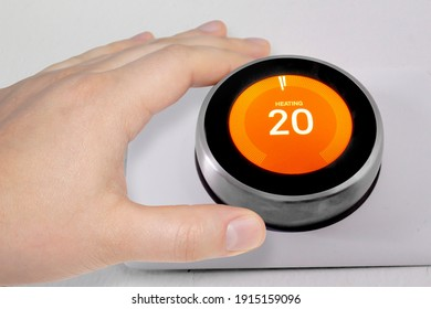 A person adjusting the temperature on a smart thermostat during winter