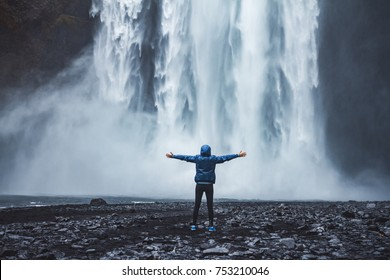 A person admirnig the beauty of Skogafoss waterfall located in Iceland