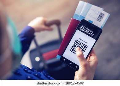 person in airport using mobile app in phone to show covid-19 test results for travel