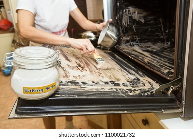 Person applying mixed baking soda onto surface of oven for effective and safe cleaning