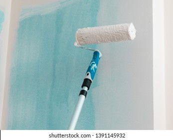 Person appplying paint on wall using roller brush. Home renovation concept.