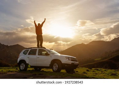 person with arms raised and on the roof of his off-road car watching the sunset on the mountain after a day of travel and adventure. Active turism. mountain activities.