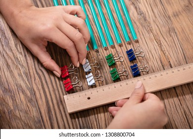 Person Arranging The Colorful Bulldog Clips With Scale On Wooden Desk