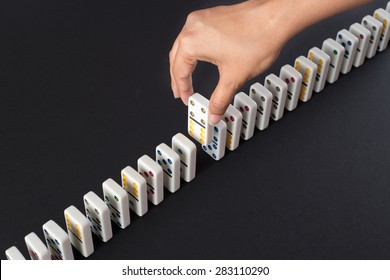 Person  arranging dominoes in a line. Concept image for business strategy and problem solving. Dominoes arranged on a black surface.