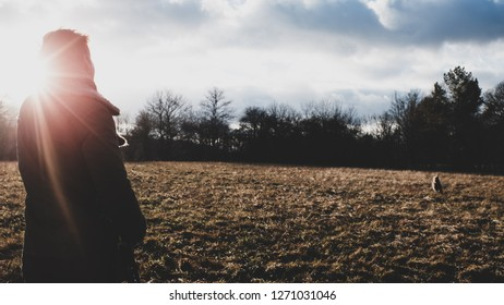 person in backlight of sunset in dramatic Autumn scenery with dog dogwalking
