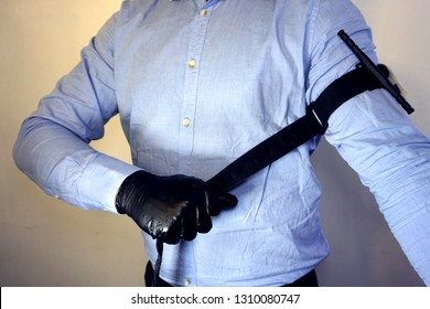 Person in black medical gloves Applies the tourniquet to his hand to prevent bleeding during the first aid. Trauma patient. Combat tactical Equipment. Combat Application Tourniquet
