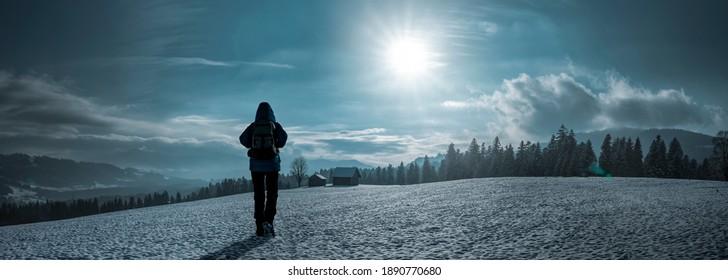 Person in blue jacket walks in the snow in Allgäu