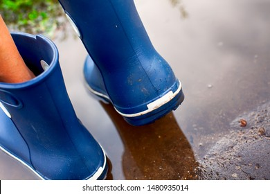 Person in blue rubber boots walking through the puddle. Back view.
