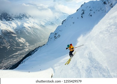 A person in bright jacket is skiing in high mountains. Chamonix valley. Sunny weather.