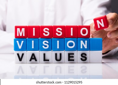 Person Building Colorful Cubic Blocks With Mission, Vision And Values Words