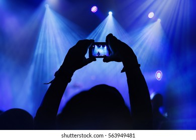 Person capturing a photo on a compact camera at a music festival.