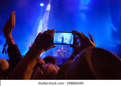 Person capturing a video on a mobile phone at a music festival.
