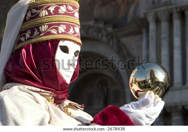 A person in carnival costume holding a gold reflective ball in St. Mark's Square