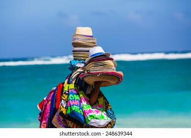 Person carrying hats and scarves on beach  with ocean in background.