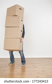 A person carrying a heavy stack of moving boxes into an empty new house.