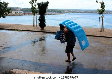 Person carrying inflatable beach mattresses and other beach stuff as protection during summer shower on paved road next to beach and calm sea with houses and cloudy sky in background