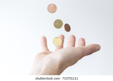 Person catching money, coins that fall down into hand. Close up and white background.