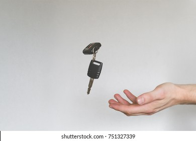 Person catching or throwing car keys. White wall in the background. Concept.