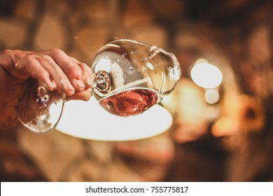 Person checking a glass of red wine. Glass of wine at an angle in front of a light to check the consistency and color of wine.