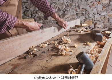 Person with chisel scraping wood off long beam on top of table next to mallet and curled wooden scraps