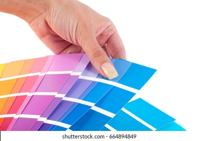 The person chooses a color in the palette for paint tinting. Colored catalog fan. The concept of design work