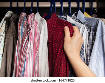 person chooses shirt in the closet of the multi-colored shirts