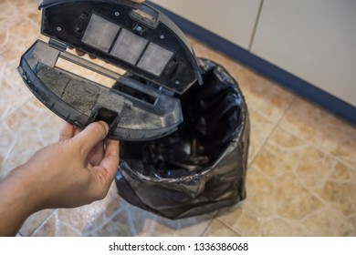 Person cleaning the dust bin of a robot vacuum cleander.