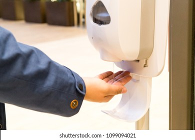 Person cleaning hand with anti-bacterial hand disinfectant from sanitizer dispenser in public mall in Japan