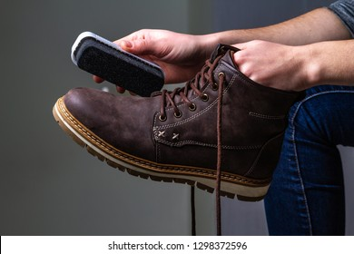 A person is cleaning men's suede casual boots with brush. Shoe shine. Footwear moisture and dirt protection. Shoe care