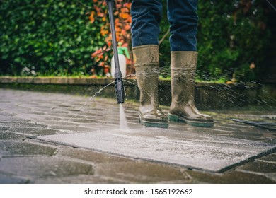 Person cleaning a rug or floor mat with the use of a high pressure water cleaner. Cleaning mats with high pressure jet while wearing plastic boots