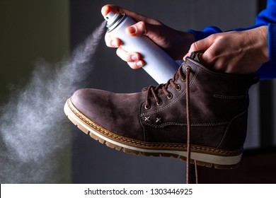 A person is cleaning and spraying agent on men's suede casual boots for protection from moisture and dirt. Shoe care