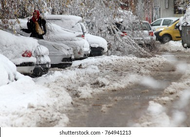 Person cleans car on a snowy icy road in the icy street after a heavy snowfall in the city of Sofia, Bulgaria on Nov 28,2017.  icy roads. icy streets