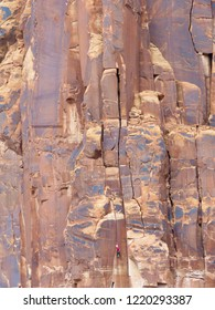 A person climbing some of the sandstone formations at Moab National Park in Moab, Utah