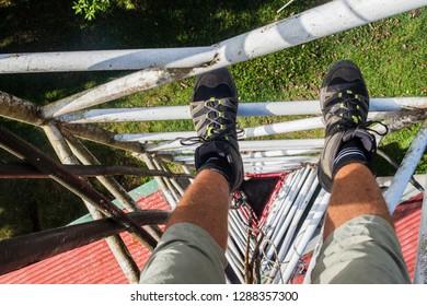 Person climbing a triangular guyed lattice mast near Santa Elena village, Costa Rica