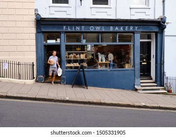 Person coming out of Flint owl Bakery on inclined High Street, Lewes, carrying bread purchase from establishment. Lewes, UK, September 12, 2019