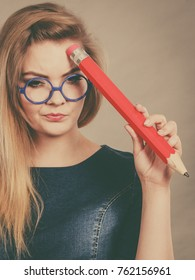 Person confused thinking seeks a solution. Pensive thoughtful student girl or business woman female teacher wearing nerdy glasses coming up with an idea, holding big red pencil. Filtered image