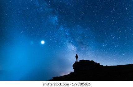 Person contemplating the vastness of the universe. Small silhouette of a man under the Milky Way and the magical starry sky. Concept of human smallness.