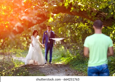 Person controls quadroopter or drone from back. Photo in sunset light on wedding day of bride and groom outdoors
