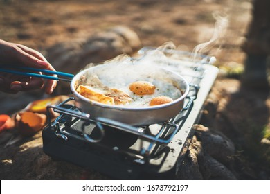 person cooking fried eggs in nature camping outdoor, cooker prepare scrambled omelette breakfast picnic on metal stove, tourist on recreation outside; campsite lifestyle