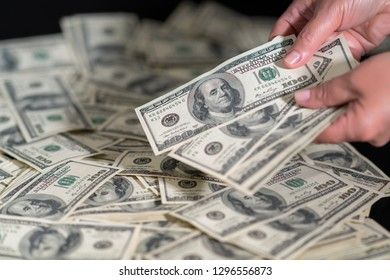 Person counting 100 dollar bills onto a pile spread out on a table in a close up on the hands