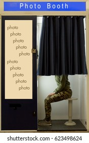 A person covered curtain sits in the photo booth. Woman makes the portrait inside photo booth. Automatic machine for the production of portrait photos on the street.