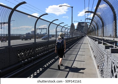 Person crossing Sydney Harbour Bridge on a  pedestrian footpath in Sydney Australia