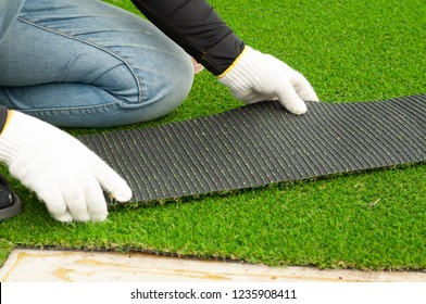 Person cut and check piece of Artificial grass. Worker install artificial turf