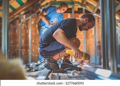 A person cutting holders, aluminium profiles or aluminium structural frames that hold drywall boards with an angle grinder in a house that is being rebuilt. Work on the roof using an angle grinder