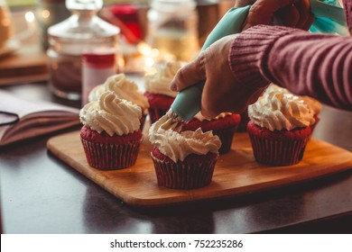 Person decorates cupcakes with whipped cream using pastry bag. Blurred background. Copy space